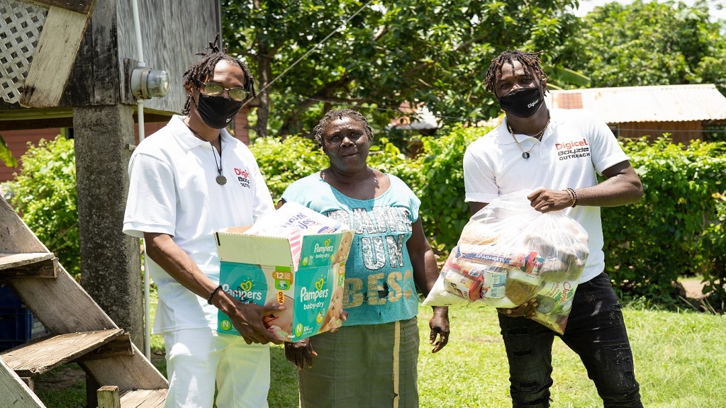 "Jalon ""Boyzie"" Olive (right), Grenadian soca artiste and entertainer is joined by Dean Hazzard (left), Corporate Care Executive, Digicel Grenada to present a food hamper and essential supplies to Pauline Charles a resident of Pearls, St Andrew last Saturday, August 15, at his joint charity drive with Digicel and Hotspot Supermarket."