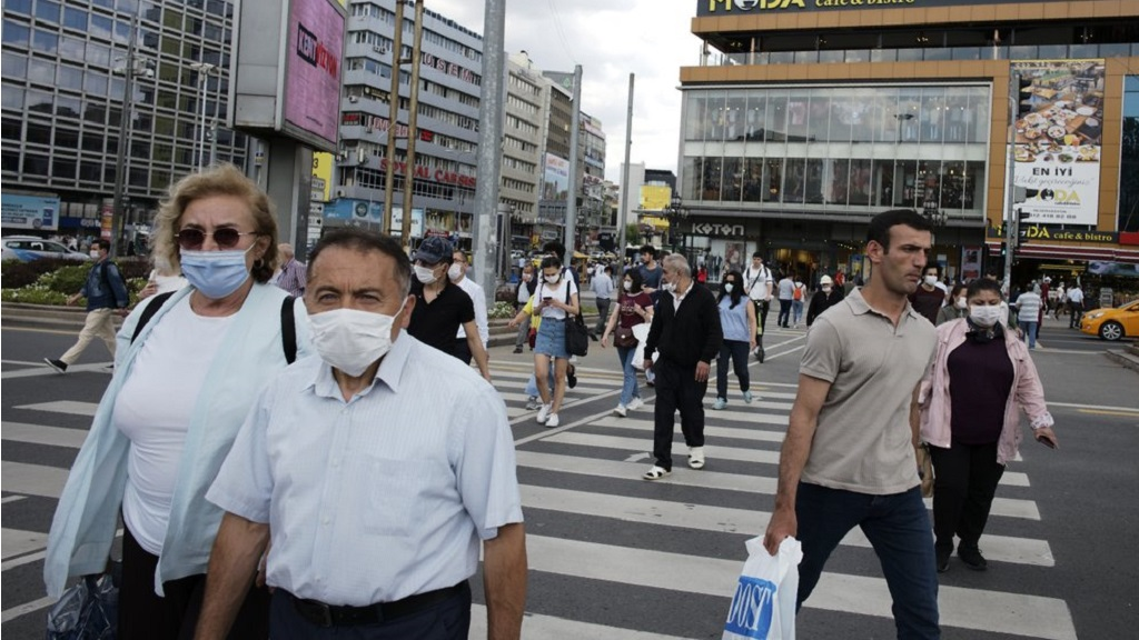 People wearing face masks to protect against the spread of coronavirus, walk in the main Kizilay Square, in Ankara, Turkey, Tuesday, June 16, 2020. Turkey has made the wearing of face masks mandatory in five more provinces, following an uptick in COVID-19 cases. Health Minister Fahrettin Koca tweeted early Tuesday that the wearing of masks is now compulsory in 42 of Turkey's 81 provinces.(AP Photo/Burhan Ozbilici)