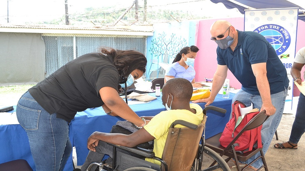 Dr Jade Jeffery, co-Founder, Mobile Medical Jamaica, examines a participant while Craig Moss-Solomon, Director of Food For The Poor, looks on.