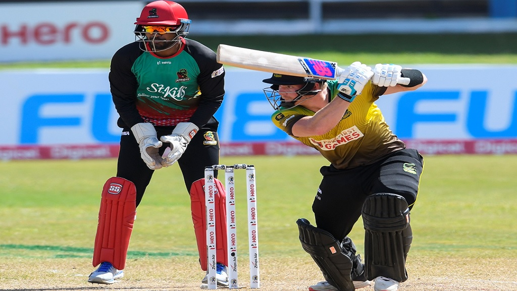 Glenn  Phillips of  Jamaica  Tallawahs  hits  a four, while  Denesh  Ramdin  of St Kitts and Nevis Patriots watches during  the 18th match of the Caribbean Premier League at Queen's Park Oval in Port-of-Spain, Trinidad and Tobago on Saturday, August 29, 2020. (Photo by Randy Brooks - CPL T20/CPL T20 via Getty Images).