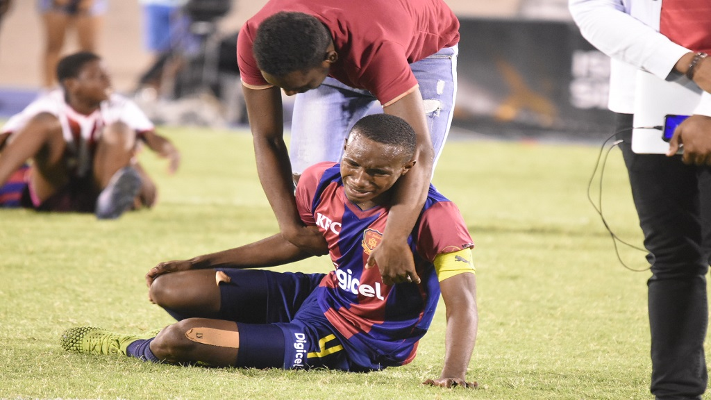 A player from St Andrew Technical High School is being consoled after his team lost 5-4 on penalties against Jamaica College in the final of the urban area ISSA/Digicel Manning Cup football competition at the National Stadium on Friday, November 29, 2019. (PHOTO: Marlon Reid).