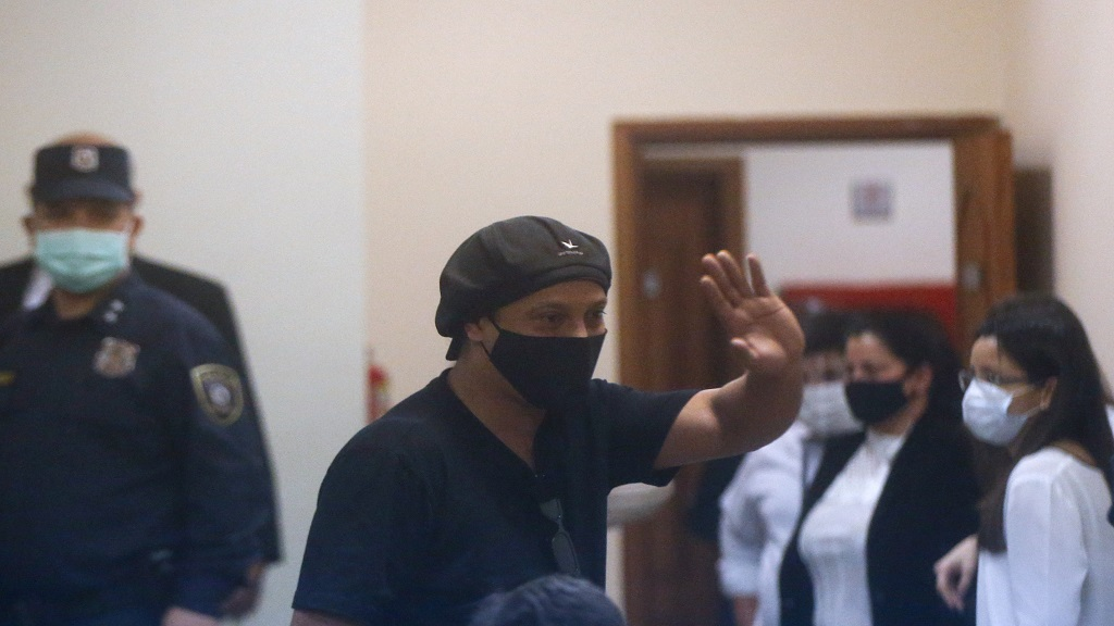 Former Brazilian football star Ronaldinho, seen through a pane of glass, waves during a court date at the Justice Palace in Asuncion, Paraguay, Monday, Aug. 24, 2020. (AP Photo/Jorge Saenz).