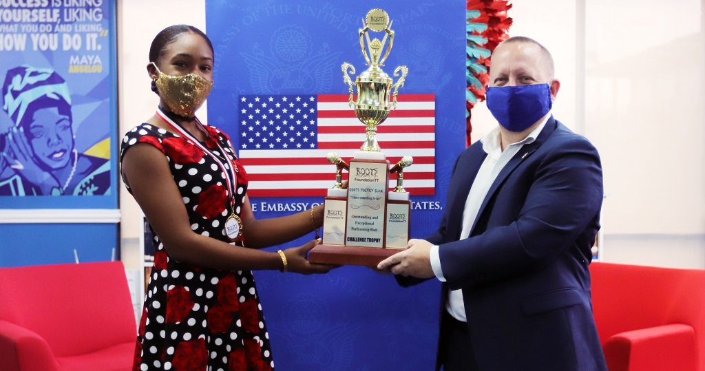 Amaris Noray receives her trophy from Chargé d'Affaires John W McIntyre for winning the Cascadoo Caribbean New Voices International (CNVI) Festival of Spoken Word 2020.