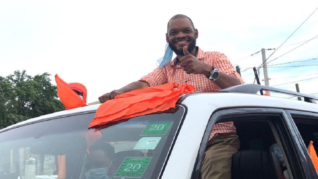 People's National Party candidate for East Central St Catherine, Raymond Pryce gives the thumbs up during a motorcade in the constituency on Friday.