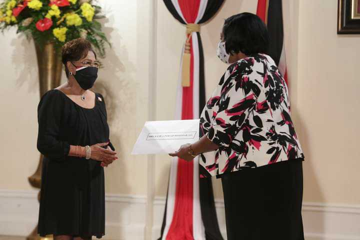 Pictured: Opposition leader Kamla Persad-Bissessar accepts her instruments of appointment. Photo via Facebook, The Office of the President of Trinidad and Tobago.