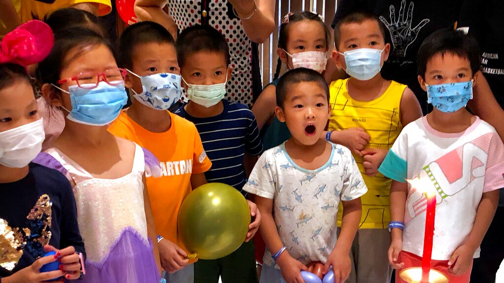 Children wearing face masks to protect against the coronavirus watch a clown magician perform at a shopping mall in Beijing, Saturday, Aug. 15, 2020. China's government reported a few dozen new confirmed coronavirus cases on Saturday, the majority of which were found in travelers arriving from overseas.