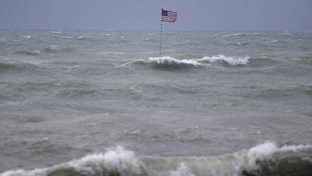 An American flag flies from the shipwreck of the Breconshire, as waves churned up by Tropical Storm Isaias crash around it, Sunday, Aug. 2, 2020, in Vero Beach, Fla. Isaias weakened from a hurricane to a tropical storm late Saturday afternoon, but was still expected to bring heavy rain and flooding as it barrels toward Florida. (AP Photo/Wilfredo Lee)
