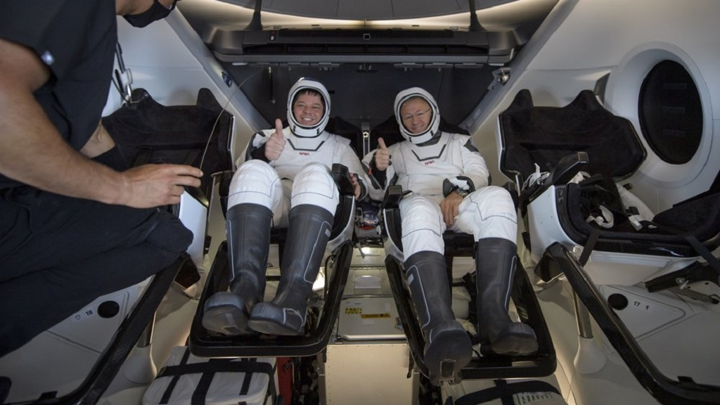 NASA astronauts Robert Behnken, left, and Douglas Hurley are seen inside the SpaceX Crew Dragon Endeavour spacecraft onboard the SpaceX GO Navigator recovery ship shortly after having landed in the Gulf of Mexico off the coast of Pensacola, Fla., Sunday, Aug. 2, 2020. (Bill Ingalls/NASA via AP)