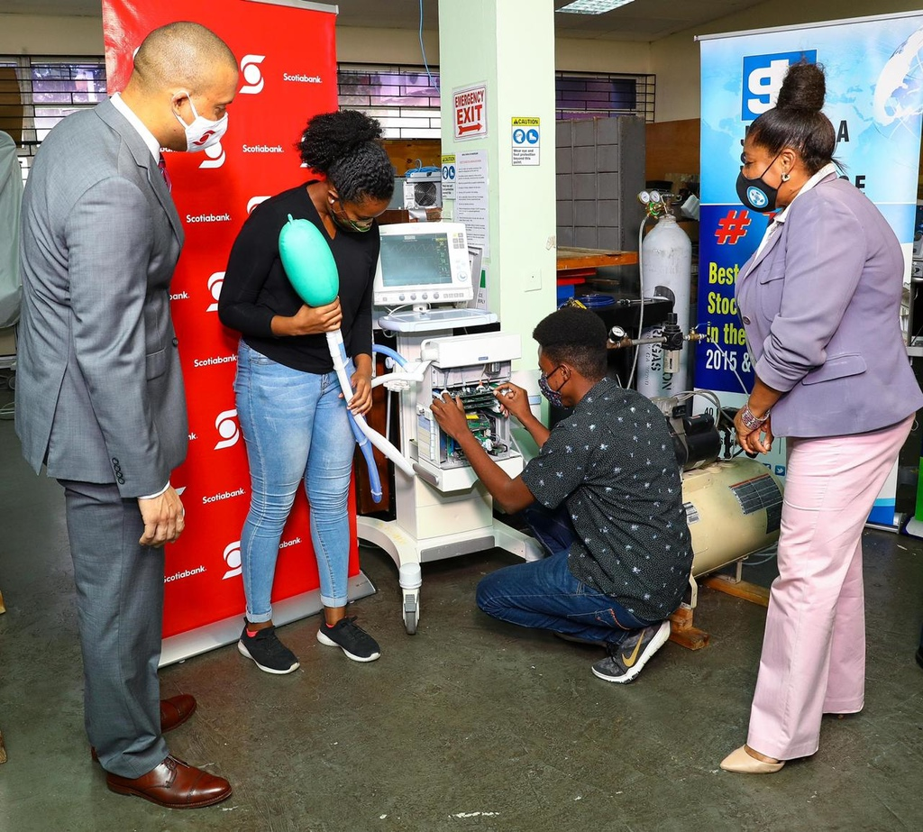 Perrin Gayle (left) , Senior Vice-President for Corporate & Commercial Banking at Scotiabank examines a simulation lung attached to a ventilator now being repaired by student engineers under the supervision of the Mona Tech Engineering Ltd. Explaining the operation is Danelle Julal (right) , an engineering student intern in the Faculty of Engineering at the University of the West Indies who has been engaged in the repairs of ventilators and other malfunctioning biomedical equipment.