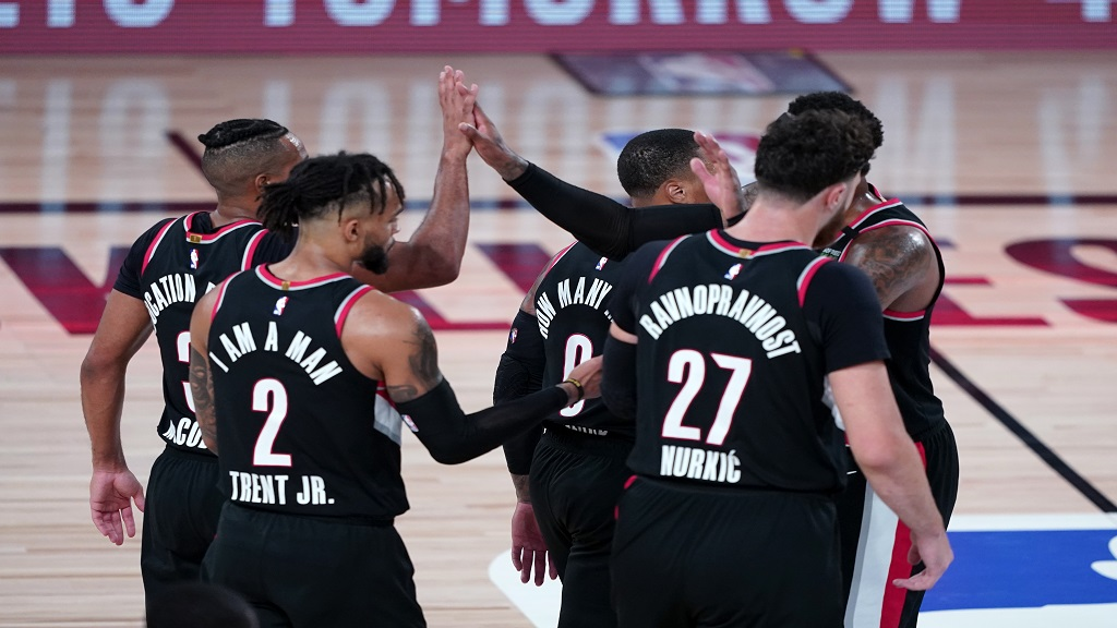 The Portland Trail Blazers celebrate after defeating the Los Angeles Lakers in an NBA basketball game Tuesday, Aug. 18, 2020, in Lake Buena Vista, Fla. Portland won 100-93. (AP Photo/Ashley Landis, Pool).