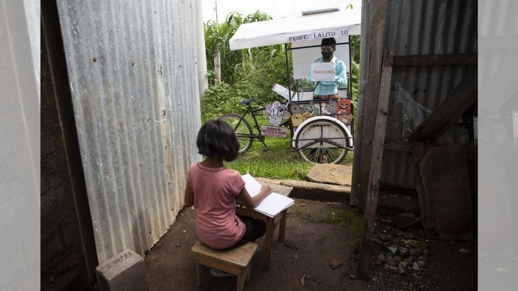 Gerardo Ixcoy teaches 12-year-old student Paola Ximena Conoz about fractions from his mobile classroom, parked just outside the door to her home. (AP Photo/Moises Castillo)