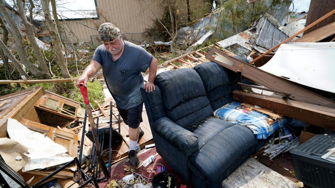 Bradley Beard walks with a shovel through his daughter's destroyed trailer home, after searching in vain for the water shutoff valve for the property in the aftermath of Hurricane Laura, Saturday, Aug. 29, 2020 in Hackberry, La. (AP Photo/Gerald Herbert)