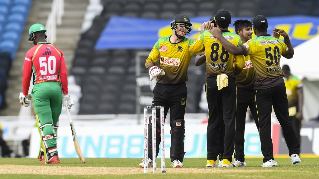 Sandeep Lamichhane (2nd right) and Glenn Phillips (2nd left) of Jamaica Tallawahs celebrate the dismissal of Sherfane Rutherford (left) of Guyana Amazon Warriors during Match 8 of the  Hero Caribbean Premier League at Brian Lara Cricket Academy on Saturday, August 22, 2020 in Tarouba, Trinidad And Tobago. (Photo by Randy Brooks - CPL T20/CPL T20 via Getty Images).