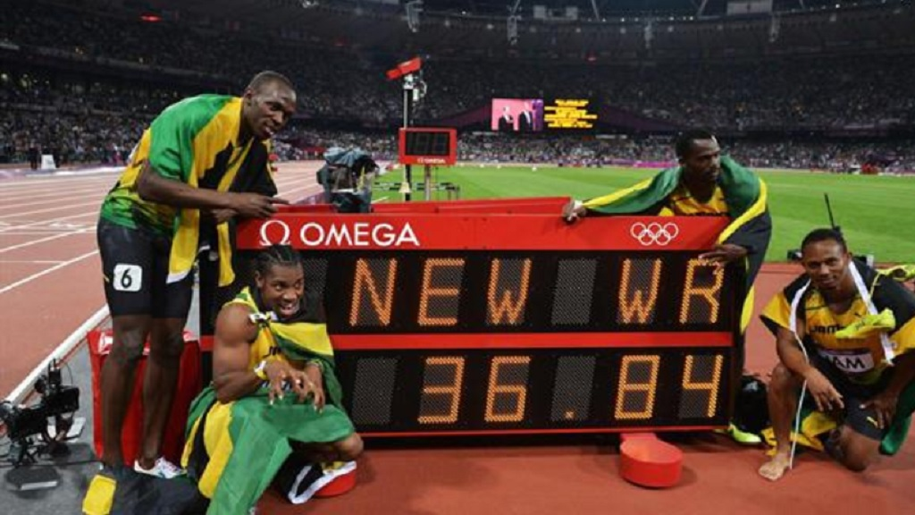Winning Jamaican team: Usain Bolt, Yohan Blake, Michael Frater and Nesta Carter next to the clock showing the new world record of 36.84 in the men's 4x100m relay final of the London 2012 Olympic Games on August 11, 2012 (World Athletics.)