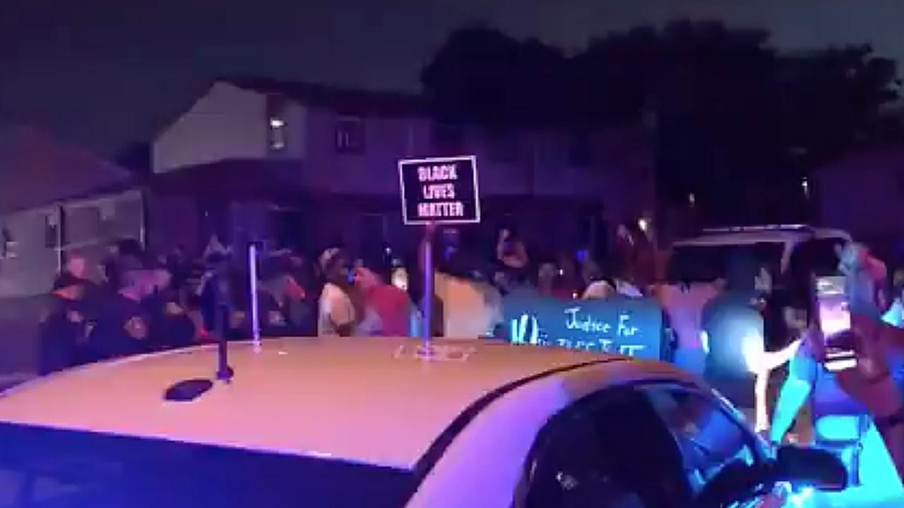 n this image made from video, protesters gather near the site of a police shooting, Sunday, Aug. 23 in Kenosha, Wisconsin. Officers deployed tear gas early Monday in an effort to disperse hundreds of people who took to the streets following a police shooting in Kenosha that also drew a harsh rebuke from the governor after a video posted on social media appeared to show officers shoot at a Black man's back seven times as he leaned into a vehicle. (WDJT-TV via AP)