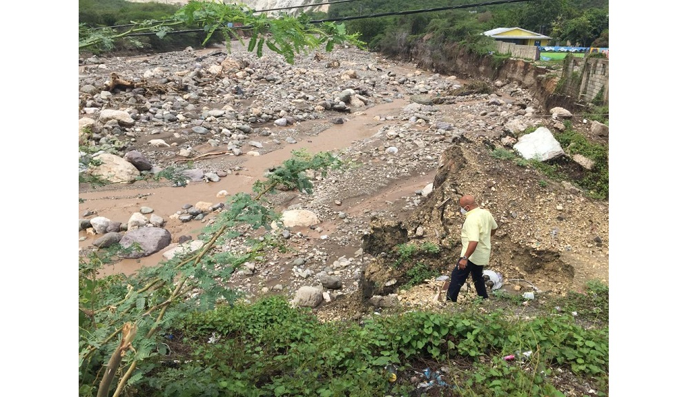 The incumbent Member of Parliamentfor Western St Thomas, James Robertson assessing the damage in Font Hill following heavy rains.