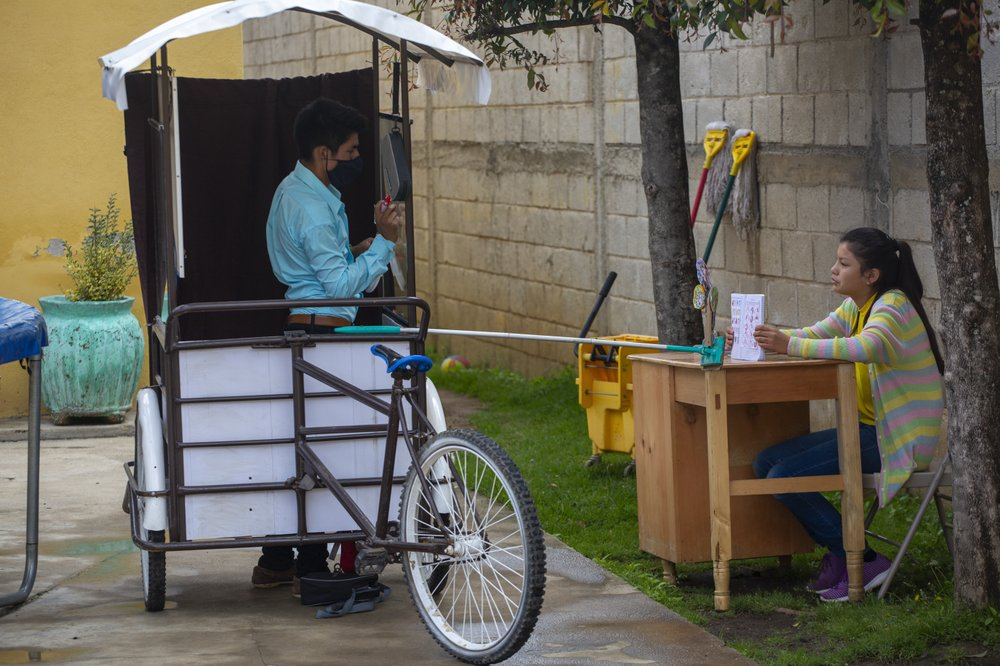 Gerardo Ixcoy teaches fractions to 14-year-old Brenda Morales, from his second-hand adult tricycle that he converted into a mobile classroom. (AP Photo/Moises Castillo)