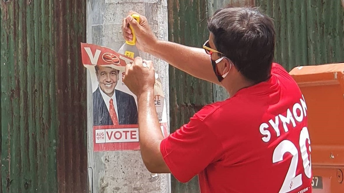 Newly elected MP for Diego Martin Central, Symon de Nobriga removes his poster from a light pole.