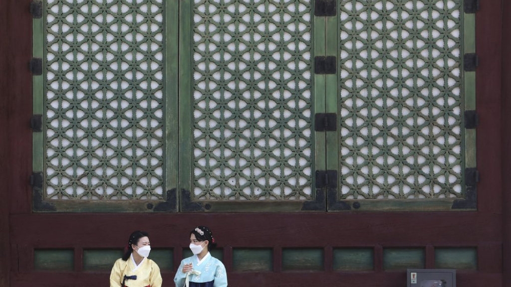Women wearing face masks to help protect against the spread of the coronavirus talk to each other at the Gyeongbok Palace in Seoul, South Korea, Monday, August 17, 2020. (AP Photo/Ahn Young-joon)