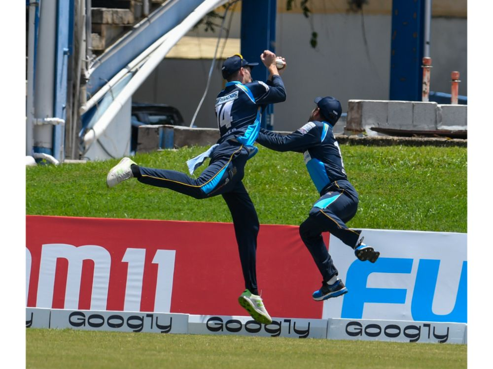 Mitchell Santner (left) and Rashid Khan of the Barbados Tridents go for a catch on the deep midwicket boundary during their six-wicket loss to the St Kitts and Nevis Patriots on 25 August 2020 at the Queen's Park Oval in Trinidad. (Photo by Randy Brooks - CPL T20/Getty Images)