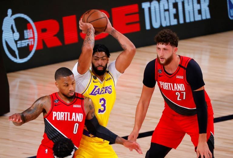 Anthony Davis (c) avec les Lakers face aux Blazers de Damian Lillard (g) et Jusuf Nurkic, le 20 août 2020 à Orlando afp.com - Kevin C. Cox