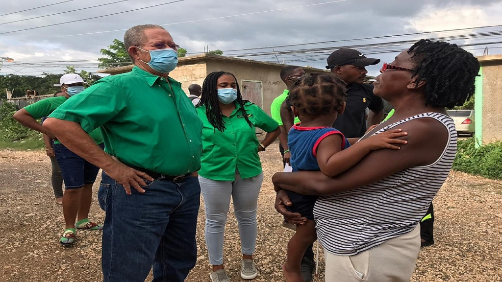 Bruce Golding (first left) and Natalie Campbell-Rodriques (centre) interact with a resident while on the campaign trail in Angels in North Central St Catherine.