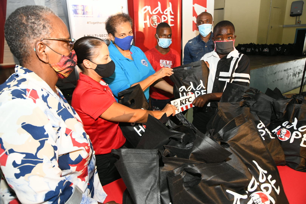 Tina Matalon (second left), Marketing Director of Restaurants of Jamaica presents a COVID care package to Damion Lodge (right) YMCA.  Looking on (from left) are Sarah Newland-Martin, General Secretary, YMCA; Greta Bogues, CEO of PSOJ; Bradley Beranford, YMCA and Kevin Downswell (second right), Brand Ambassador. The presentation was made at the YMCA building to children under the guidance of YMCA and Boys Town Foundation, which was founded by YMCA.