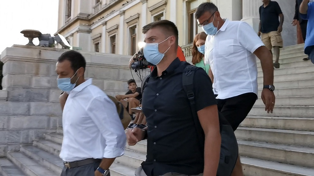 Manchester United player Harry Maguire's father, Alan, background leaves a court building with two other men after his son was found guilty of assault and attempting to bribe a police officer, on the Aegean island of Syros, Greece, Tuesday, Aug. 25, 2020. Maguire has been found guilty of assault at a trial and handed a 21-month suspended sentence following his arrest after a brawl last week on the island of Mykonos, court officials in Greece said. (Giorgos Solaris/InTime News via AP).
