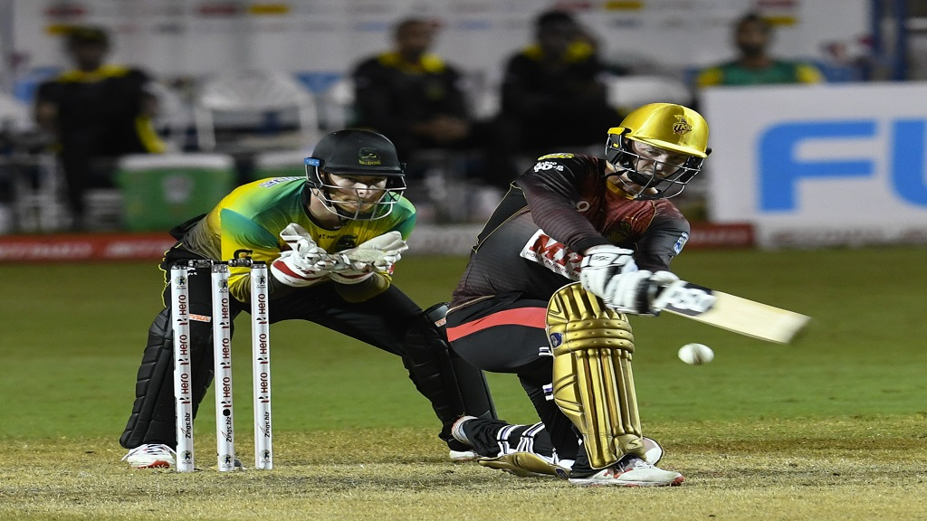 Colin Munro of Trinbago Knight Riders hits a four while wicketkeeper Glenn Phillips of Jamaica Tallawahs watches during the sixth match of the Hero Caribbean Premier League at the Brian Lara Cricket Academy on Thursday, August 20, 2020 in Tarouba, Trinidad And Tobago. (Photo by Randy Brooks - CPL T20/CPL T20 via Getty Images).