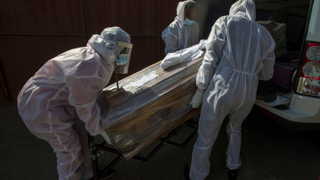 Funeral home workers in protective suits carry the coffin of a woman who died from COVID-19 into a hearse in Katlehong, near Johannesburg, South Africa, Tuesday, July 21, 2020.  (AP Photo/Themba Hadebe)