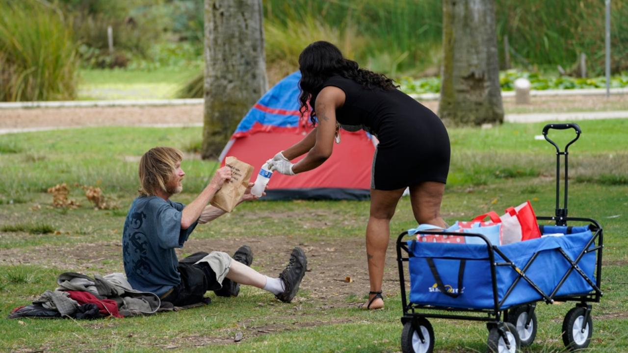 "Samantha Garvin, a personal trainer, right, makes her ""Make a difference Monday,"" a personal project delivering bagged lunches and cold bottled water to homeless people camping at Echo Park in Los Angeles Monday, Aug. 17, 2020. (AP Photo/Damian Dovarganes)"