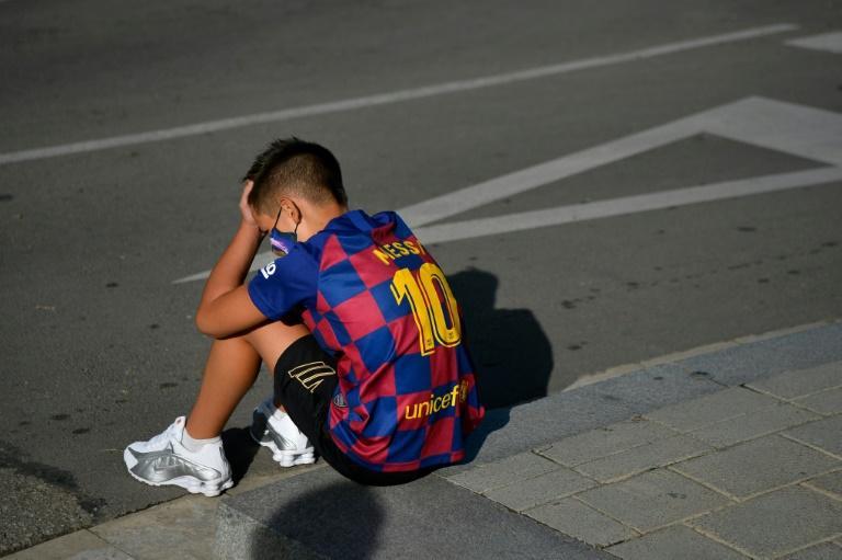 Un garçon avec le maillot de Lionel Messi attend le 30 août 2020 devant le centre d'entraînement du FC Barcelone où les joueurs devaient venir pour un dépistage du Covid afp.com - Pau BARRENA
