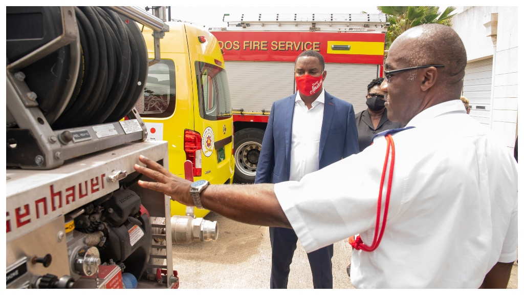 Minister of Home Affairs, Information and Public Affairs, Wilfred Abrahams and Director of Public Affairs, Pat Parris, listen attentively as Chief Fire Officer, Errol Maynard, explains the equipment on the fire tender.