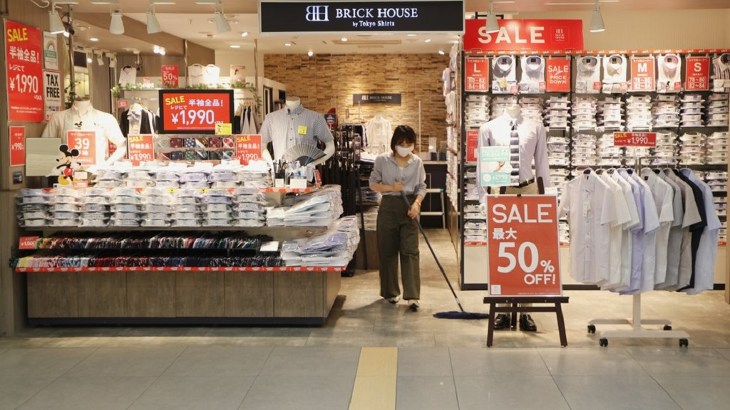 A worker mops the floor of a retail store at a shopping center in Tokyo on Monday, Aug. 17, 2020. Japan's economy shrank at annual rate of 27.8% in April-June, the worst contraction on record, as the coronavirus pandemic slammed consumption and trade, according to government data released Monday. (AP Photo/Hiro Komae)