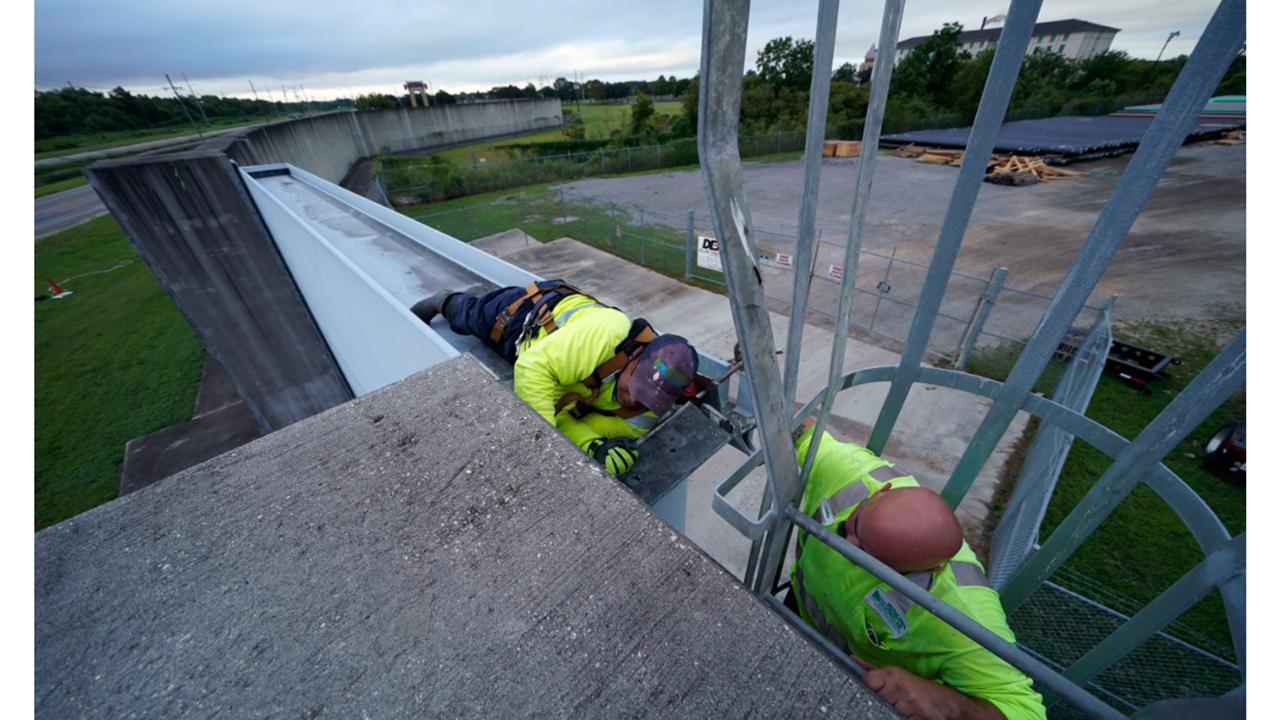 Workers for the Southeast Louisiana Flood Protection Authority - West, close floodgates in Harvey, La., just outside New Orleans, Monday, Aug. 24, 2020, in advance of Tropical Storm Marco, expected to come near the Southern Louisiana coast. (AP Photo/Gerald Herbert)