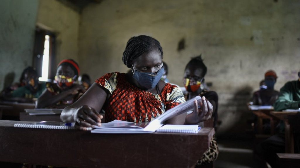 "A trainee reads a handbook on coronavirus prevention, at a training session for community health workers conducted by the national NGO ""Health Link"" in Gumbo, on the outskirts of Juba, South Sudan Tuesday, Aug. 18, 2020. (AP Photo/Charles Atiki Lomodong)"