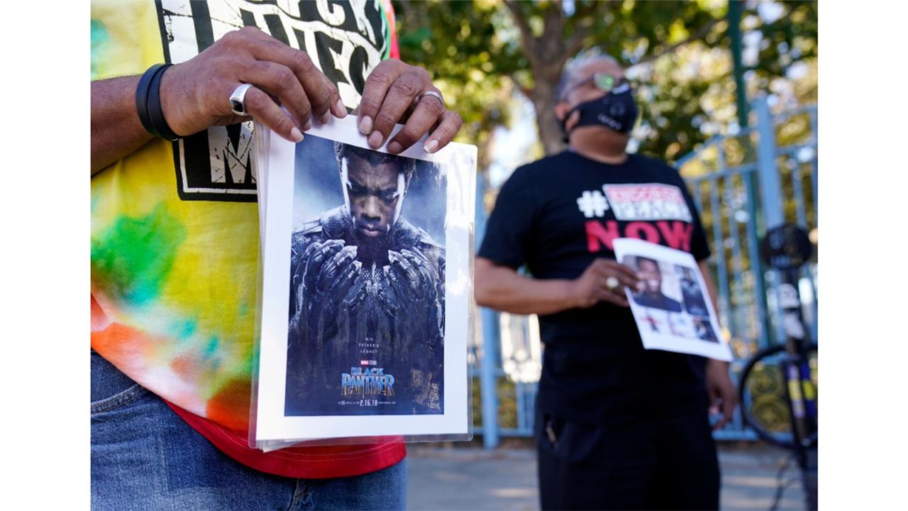 "A portrait of the late actor Chadwick Boseman as the character T'Challa in the 2018 film ""Black Panther"" is held by a participant in a news conference celebrating his life, Saturday, Aug. 29. 2020, in Los Angeles. Boseman died Friday at 43 after a four-year fight with colon cancer. (AP Photo/Chris Pizzello)"