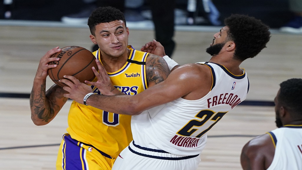Los Angeles Lakers' Kyle Kuzma (0) drives to the basket against Denver Nuggets' Jamal Murray (27) during the second half of an NBA basketball game Monday, Aug. 10, 2020, in Lake Buena Vista, Fla. (AP Photo/Ashley Landis, Pool).