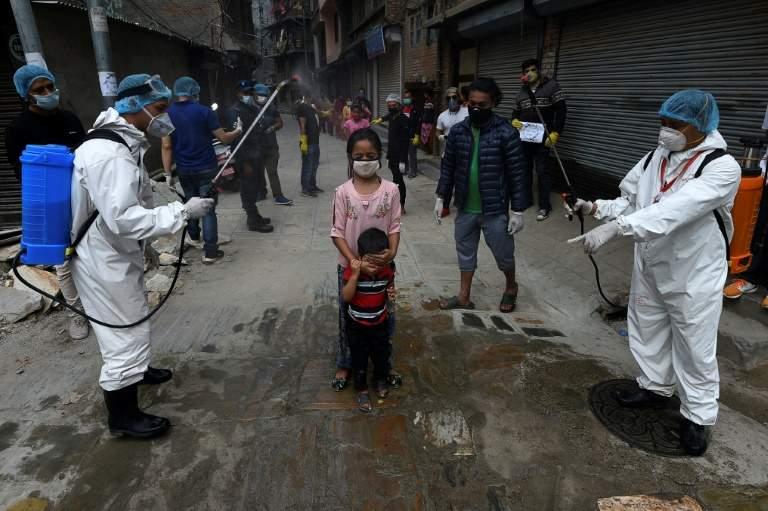 Des agents sanitaires aspergent des enfants d'une solution désinfectante, le 7 mai à Katmandou, au Népal. Crédit: PRAKASH MATHEMA/AFP