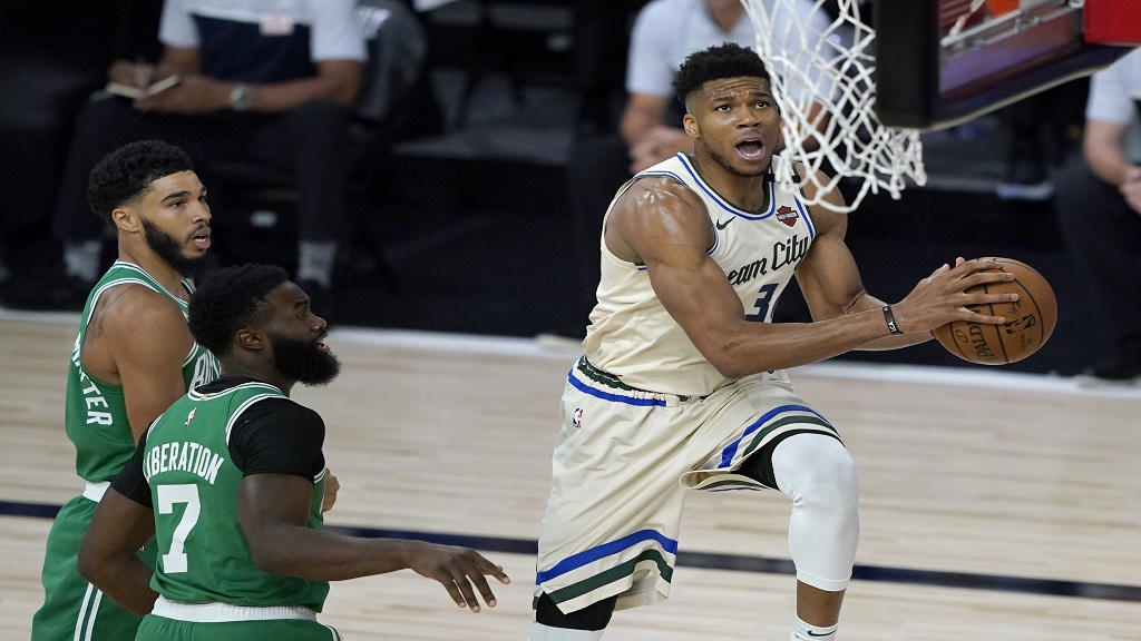 Milwaukee Bucks' Giannis Antetokounmpo, right, heads to the basket past Boston Celtics' Jaylen Brown (7) during the first half of an NBA basketball game Friday, July 31, 2020, in Lake Buena Vista, Fla. (AP Photo/Ashley Landis, Pool).