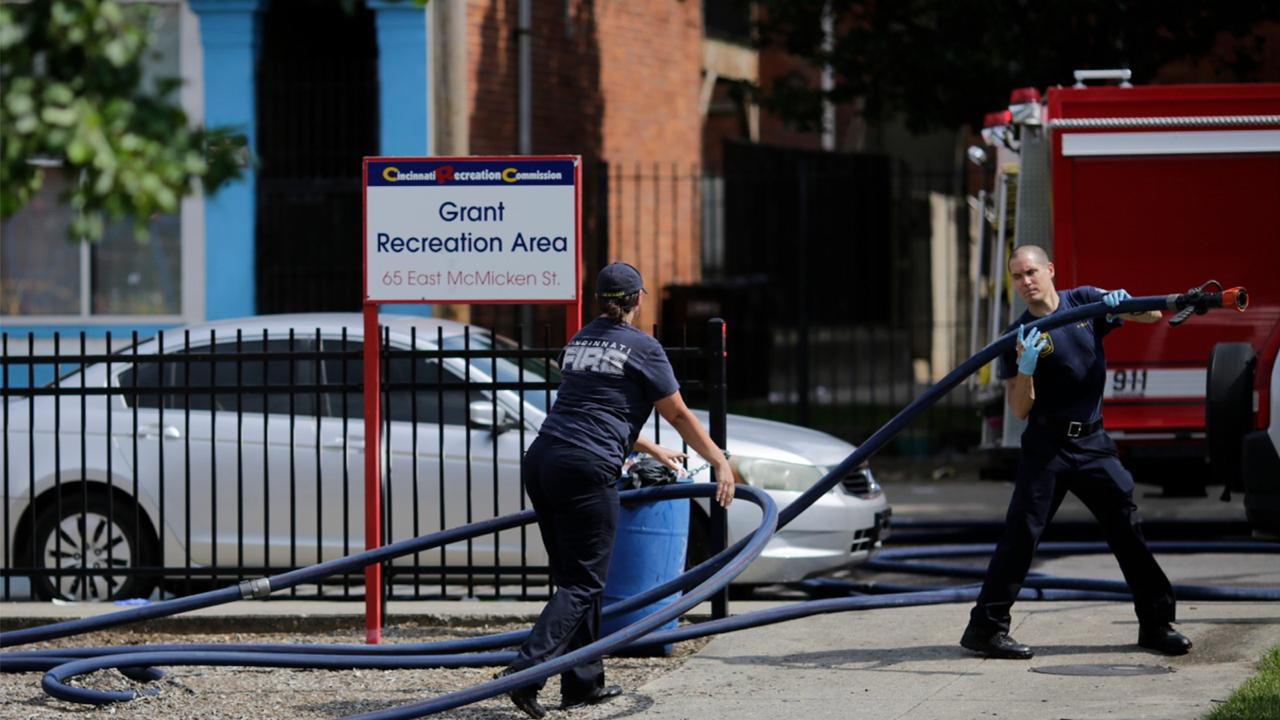 Cincinnati firefighters use bleach and a hose to clean and remove pools of blood left at the scene of a mass shooting near Grant Park in the Over-the-Rhine neighborhood of Cincinnati on Sunday, Aug. 16, 2020. Police confirm that multiple people are injured and at least three are dead after three separate shootings occurred in the city of Cincinnati within 90 minutes early Sunday morning. (Sam Greene/The Cincinnati Enquirer via AP)