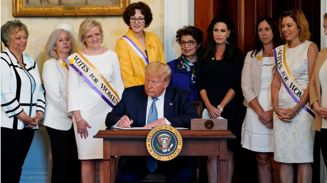 President Donald Trump signs a proclamation recognizing the 100th anniversary of the ratification of the 19th Amendment, Tuesday, Aug. 18, 2020, in the Blue Room of the White House in Washington. (AP Photo/Patrick Semansky)