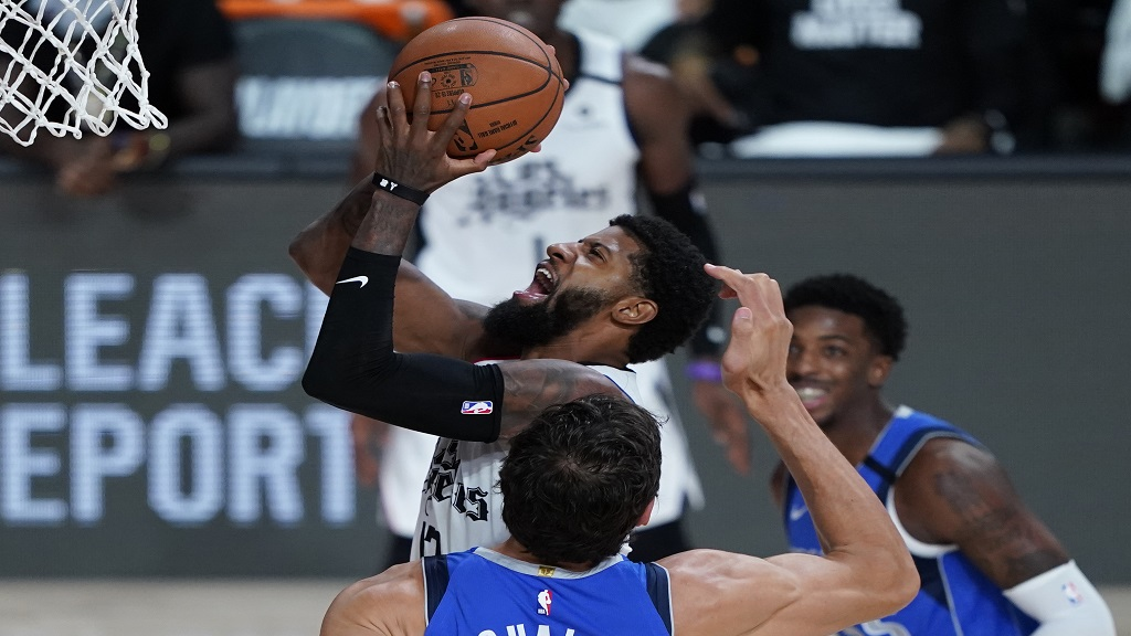 Los Angeles Clippers' Paul George, centre, drives to the basket against the Dallas Mavericks during the second half of an NBA basketball first round playoff game Tuesday, Aug. 25, 2020, in Lake Buena Vista, Fla. (AP Photo/Ashley Landis, Pool).