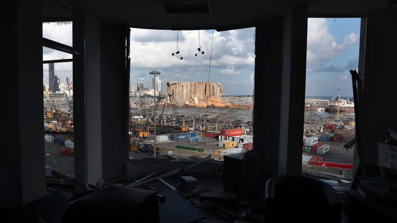 The scene of the explosion that hit the seaport of Beirut is seen through a damaged apartment in Beirut, Lebanon, Monday, Aug. 10, 2020. (AP Photo/Bilal Hussein)