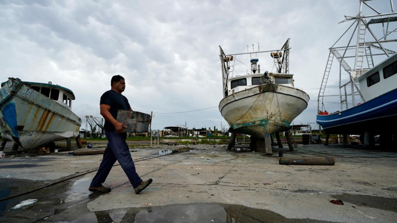 Mike Bartholemey places extra blocks under his recently dry docked shrimp boat, out of concern for strong winds, in Empire, La., Sunday, Aug. 23, 2020, in advance of Hurricane Marco, expected to make landfall on the Southern Louisiana coast. (AP Photo/Gerald Herbert)