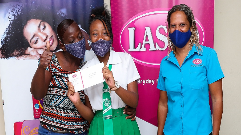 Mom, Marjorie Wright (left) shares a sweet embrace with her star achiever and 2020 LASCO Curves Primary Exit Profile (PEP) Scholarship recipient Miquandre Wright (centre) during a special ceremony at LASCO Distributors Limited in White Marl, St. Catherine on Wednesday, August 19, 2020. LASCO Beverage Marketing Manager Danielle Cunningham joins the moment.