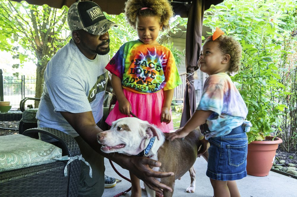 Omar Brooks, and his daughters, five-year-old Zaida, and two-year-old Waverly, pet Maisie Mae, a foster dog at Bridge To Home Animal Rescue. (Andrew Rush/Pittsburgh Post-Gazette via AP)