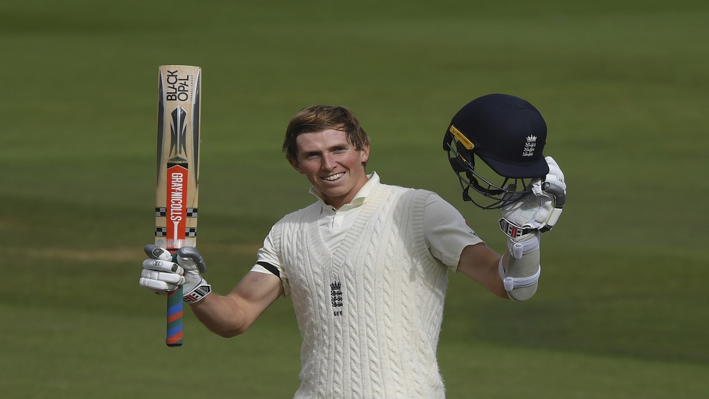 England's Zak Crawley raises his bat and helmet to celebrate scoring a century during the first day of the third cricket Test match against Pakistan, at the Ageas Bowl in Southampton, England, Friday, Aug. 21, 2020. (Mike Hewitt/Pool via AP).