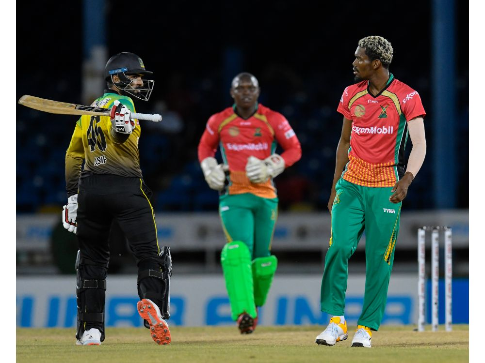 Jamaica Tallawahs batsman Asif Ali (left) swings reacts angrily after being dismissed by Guyana Amazon Wariors Keemo Paul (right) during Game 12 of the 2020 Hero Caribbean Premier League at the Queen's Park Oval in Port-of-Spain, Trinidad. (Photo by Randy Brooks - CPL T20/Getty Images)