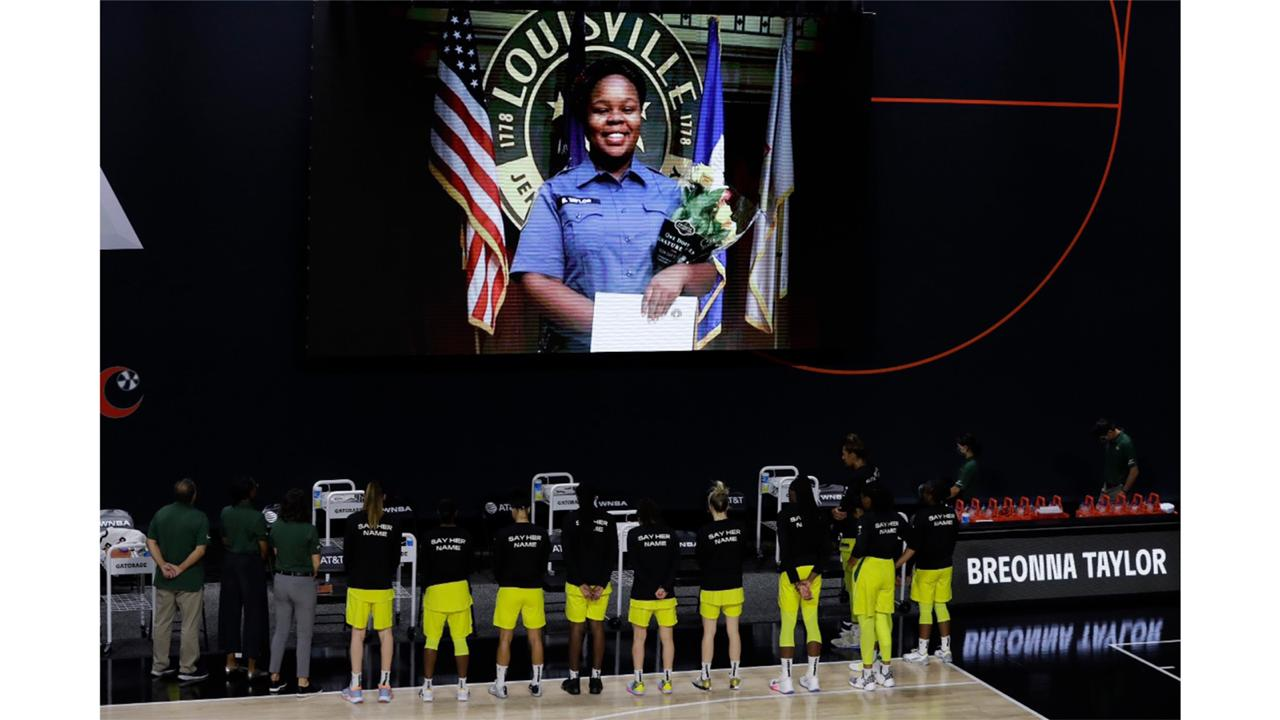 In this July 30, 2020, file photo members of the Seattle Storm stand in front of a photo of Breonna Taylor before a WNBA basketball game against the Washington Mystics in Bradenton, Fla.   (AP Photo/Chris O'Meara, File)